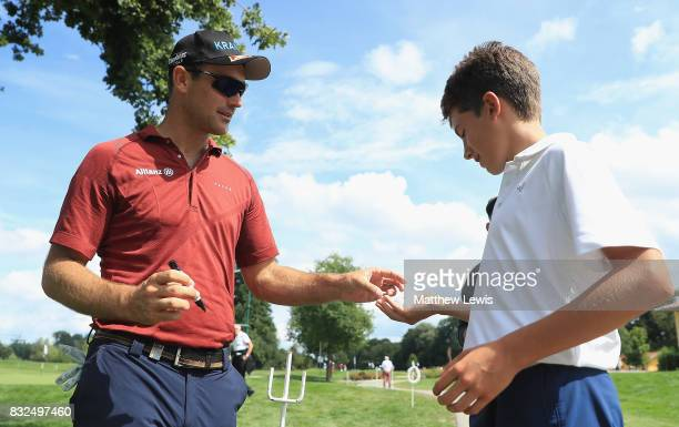Florian Fritsch of Germany signs a golf ball for a young fan ahead of the Saltire Energy Paul Lawrie Matchplay at Golf Resort Bad Griesbach on August...