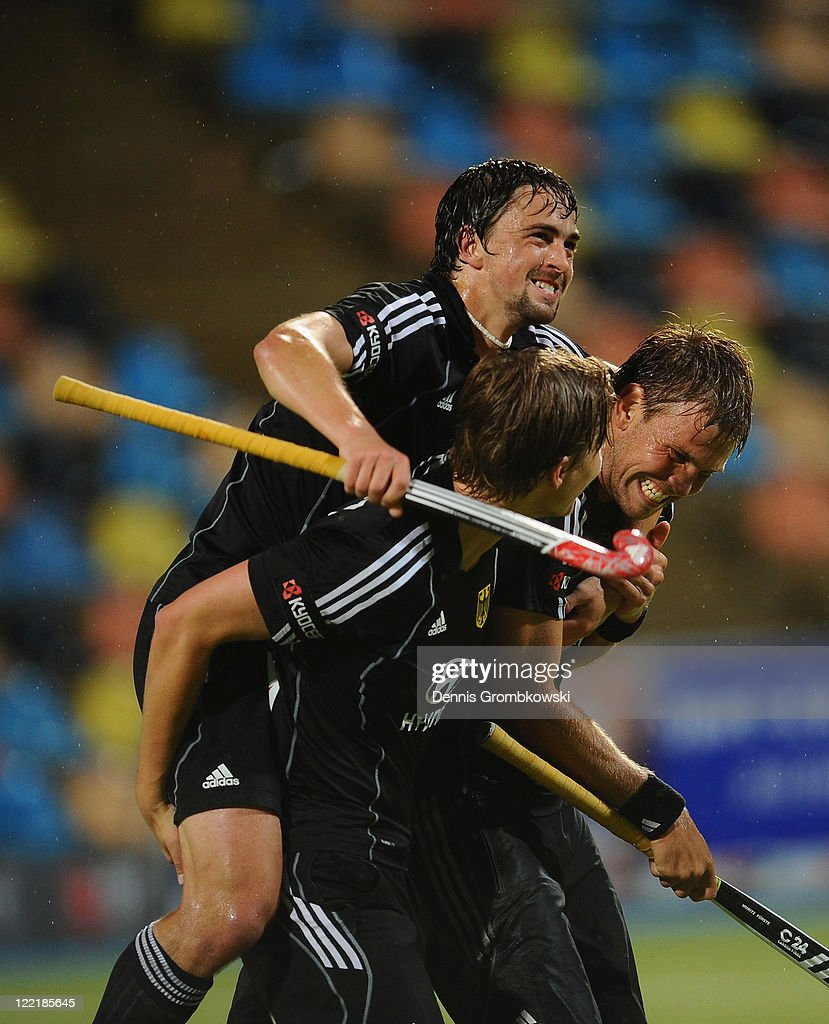 Florian Fuchs (L) of Germany and team mates Linus Butt (C) and Moritz Fuerste celebrate after winning the Men's Eurohockey 2011 semi final match between Germany and England at Warsteiner HockeyPark on August 26, 2011 in Moenchengladbach, Germany.