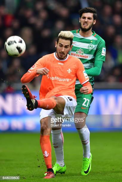 Florian Grillitsch of Bremen is challenged by Mario Vrancic of Darmstadt during the Bundesliga match between Werder Bremen and SV Darmstadt 98 at...