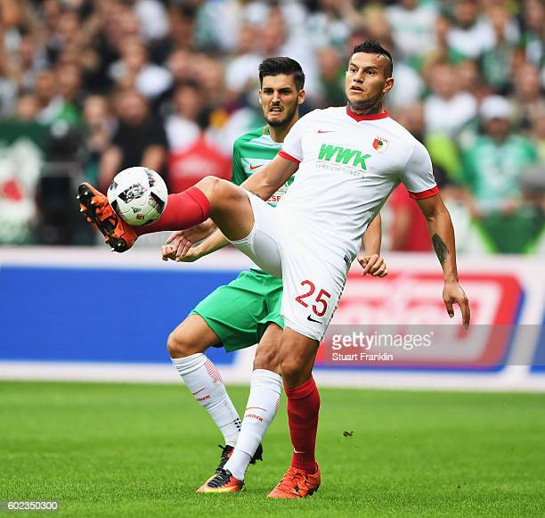 Florian Grillitsch of Bremen is challenged by Raul Bobadilla of Augsburg during the Bundesliga match between Werder Bremen and FC Augsburg at...