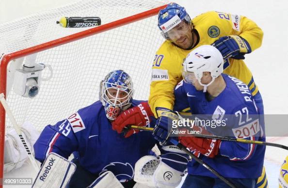 Florian Hardy and Brian Henderson of France catch Joel Lundqvist of Sweden during the 2014 IIHF World Championship between Sweden and France at...