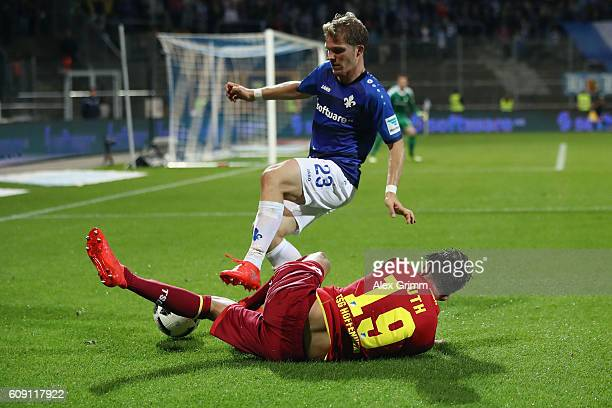 Florian Jungwirth of Darmstadt is challenged by Mark Uth of Hoffenheim during the Bundesliga match between SV Darmstadt 98 and TSG 1899 Hoffenheim at...