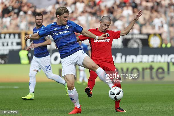 Florian Jungwirth of Darmstadt is challenged by Mijat Gacinovic of Frankfurt during the Bundesliga match between SV Darmstadt 98 and Eintracht...
