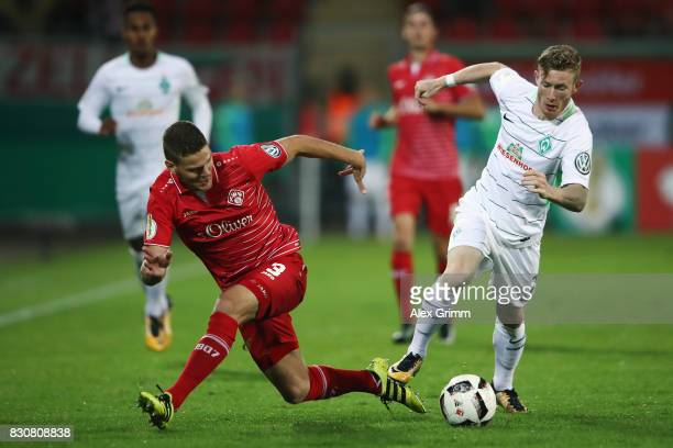 Florian Kainz 8r9 of Bremen is challenged by Anthony Syhre of Wuerzburg during the DFB Cup first round match between Wuerzburger Kickers and SV...