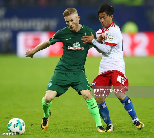 Florian Kainz of Bremen fights for the ball with Tatsuya Ito of Hamburg during the Bundesliga match between Hamburger SV and SV Werder Bremen at...