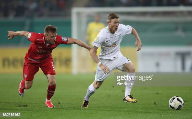 Florian Kainz of Bremen is challenged by Maximilian Ahlschwede of Wuerzburg during the DFB Cup first round match between Wuerzburger Kickers and SV...