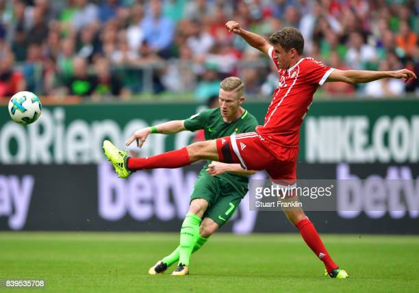 Florian Kainz of Bremen is challenged by Thomas Mueller of Muenchen during the Bundesliga match between SV Werder Bremen and FC Bayern Muenchen at...