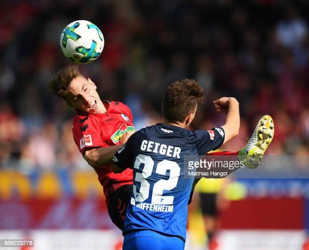 Florian Kath of SC Freiburg is challenged by Dennis Geiger of 1899 Hoffenheim during the Bundesliga match between SportClub Freiburg and TSG 1899...