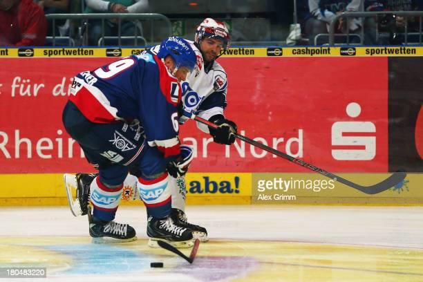 Florian Kettemer of Mannheim is challenged by Tyler Beechey of Schwenningen during the DEL match between Adler Mannheim and Schwenninger Wild Wings...