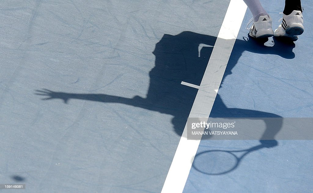 Florian Mayer of Germany casts a shadow as he prepares to serve against Bernard Tomic of Australia during their second round match at the Sydney International tennis tournament on January 9, 2013.