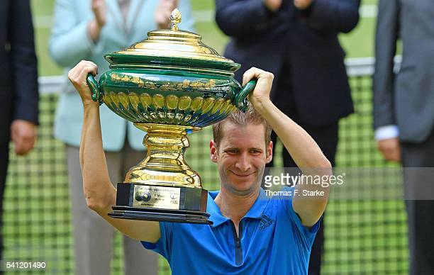Florian Mayer of Germany lifts the winners cup after winning the final match of the Gerry Weber Open against Alexander Zverev of Germany at Gerry...