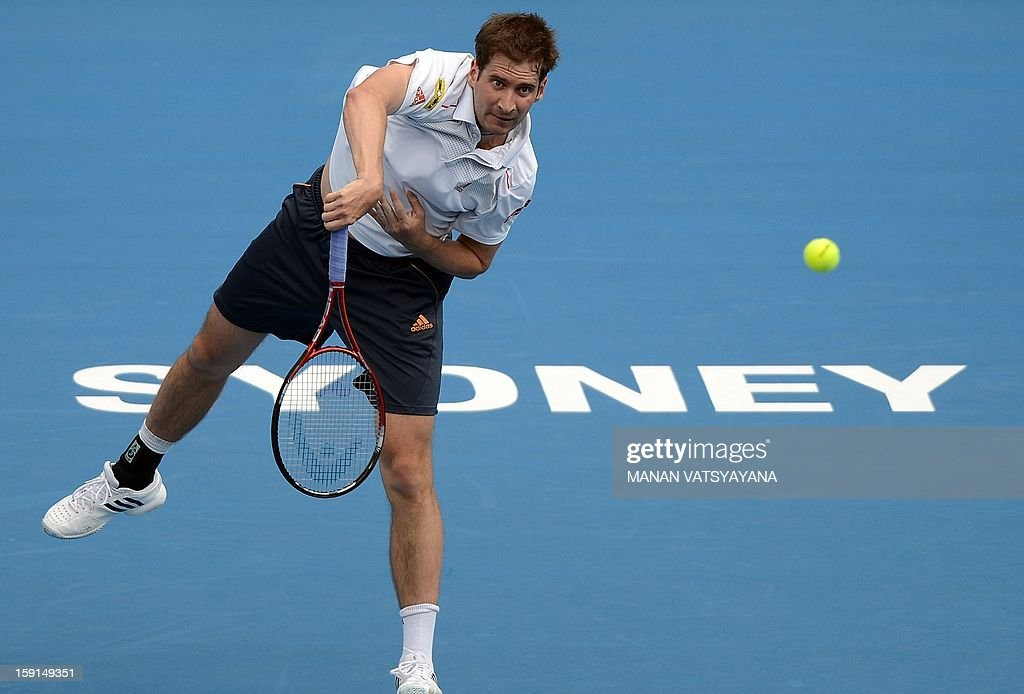 Florian Mayer of Germany serves against Bernard Tomic of Australia during their second round match at the Sydney International tennis tournament on January 9, 2013. AFP PHOTO / MANAN VATSYAYANA USE