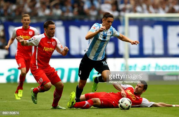 Florian Neuhaus of 1860 Muenchen and Andreas Geipl and Marco Gruettner of Jahn Regensburg compete for the ball during the Second Bundesliga Playoff...