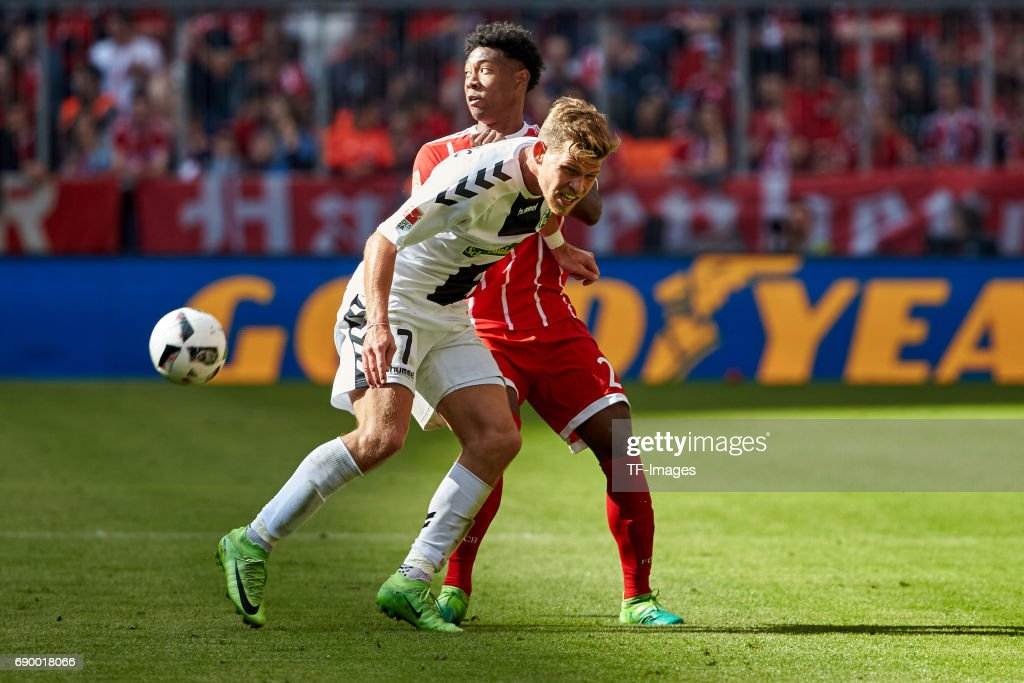 Florian Niederlechner of Freiburg and David Alaba of Bayern Muenchen battle for the ball during the Bundesliga match between Bayern Muenchen and SC Freiburg at Allianz Arena on May 20, 2017 in Munich, Germany.