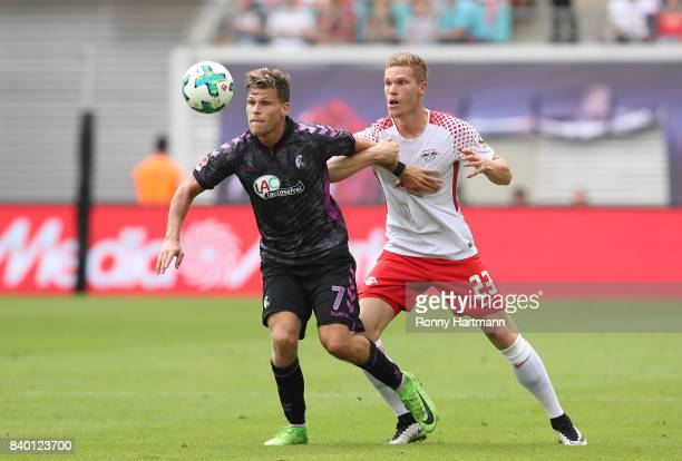 Florian Niederlechner of Freiburg and Marcel Halstenberg of Leipzig compete during the Bundesliga match between RB Leipzig and SportClub Freiburg at...