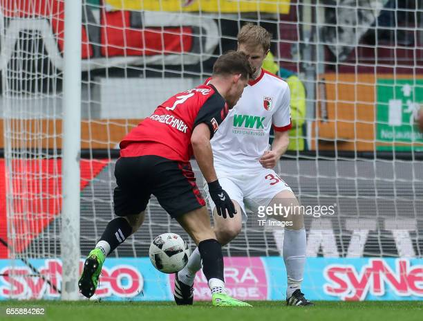 Florian Niederlechner of Freiburg and Martin Hinteregger of Augsburg battle for the ball during the Bundesliga match between FC Augsburg and SC...