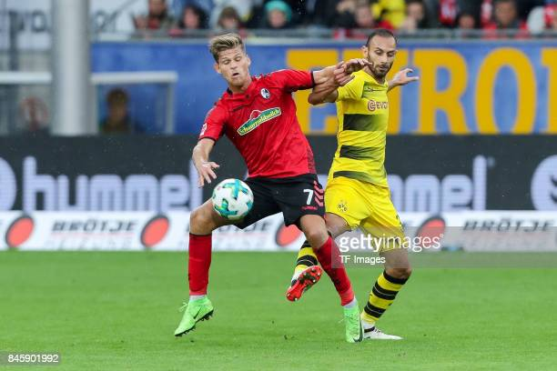 Florian Niederlechner of Freiburg and Oemer Toprak of Dortmund battle for the ball during the Bundesliga match between SportClub Freiburg and...