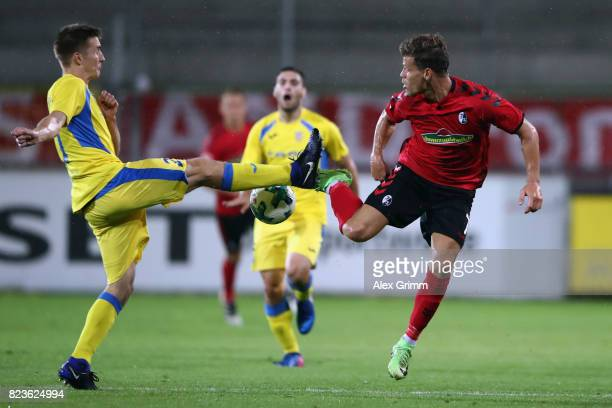 Florian Niederlechner of Freiburg is challenged by Gaber Dobrovolj of Domzale during the UEFA Europa League Third Qualifying Round first leg match...