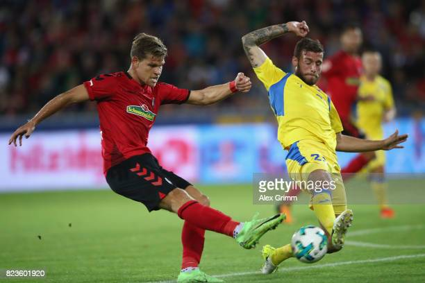Florian Niederlechner of Freiburg is challenged by Miha Blazic of Domzale during the UEFA Europa League Third Qualifying Round first leg match...