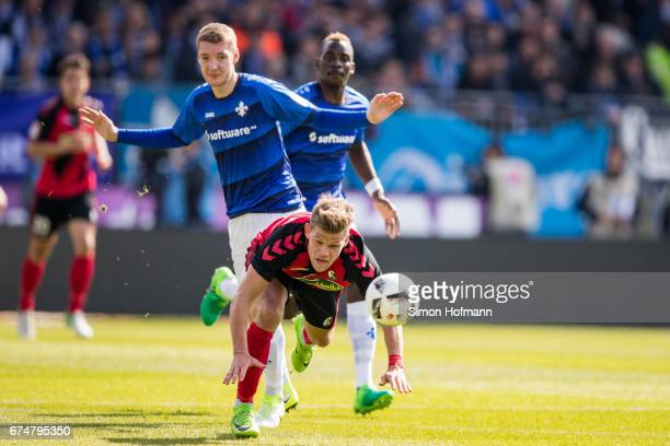 Florian Niederlechner of Freiburg is challenged by Patrick Banggaard of Darmstadt during the Bundesliga match between SV Darmstadt 98 and SC Freiburg...