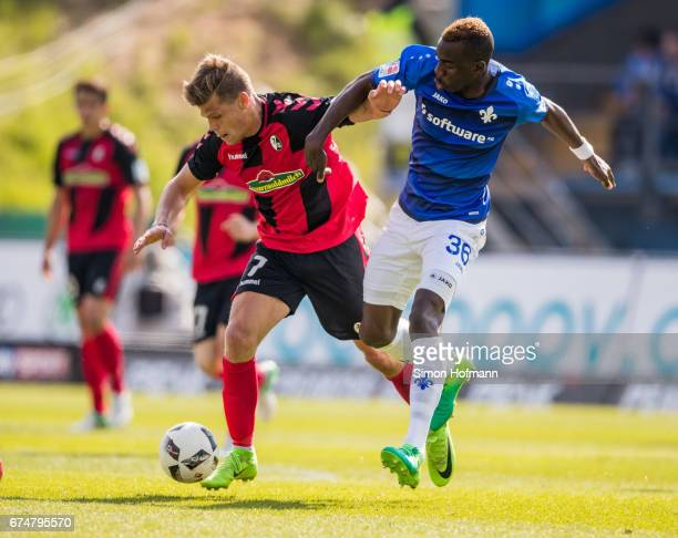 Florian Niederlechner of Freiburg is challenged by Wilson Kamavuaka of Darmstadt during the Bundesliga match between SV Darmstadt 98 and SC Freiburg...