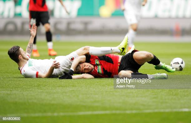 Florian Niederlechner of Freiburg is tackled by Jeffrey Gouweleeuw of Augsburg during the Bundesliga match between FC Augsburg and SC Freiburg at WWK...