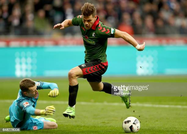 Florian Niederlechner of Freiburg on his way to score his teams first goal against goalkeeper Lukas Hradecky of Frankfurt during the Bundesliga match...