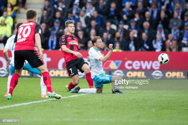 Florian Niederlechner of Freiburg scores his team's first goal against Benedikt Hoewedes of Schalke during the Bundesliga match between SC Freiburg...