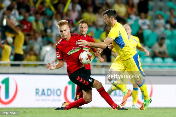 Florian Niederlechner of SC Freiburg and Amadej Vetrih of NK Domzale battle for the ball during the UEFA Europa League Third Qualifying Round match...