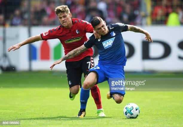 Florian Niederlechner of SC Freiburg challenges Lukas Rupp of 1899 Hoffenheim during the Bundesliga match between SportClub Freiburg and TSG 1899...