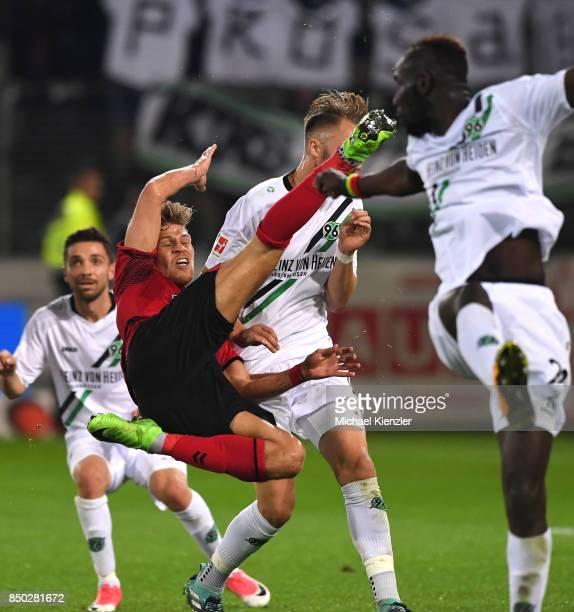 Florian Niederlechner of SC Freiburg challenges Salif Sane of Hannover 96 during the Bundesliga match between Sport Club Freiburg and Hannover 96 at...