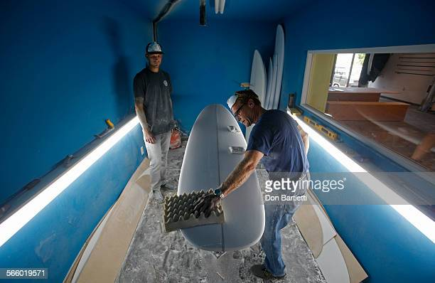 VISTA CA Florian Saylor left owner of Shaper Supply Company in Mar Vista CA teaches customer Chris Erskine how to sand a surfboard blank at the new...