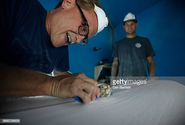 VISTA CA Florian Saylor right owner of Shaper Supply Company in Mar Vista CA watches customer Chris Erskine plane the spine of a surfboard blank at...