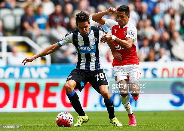 Florian Thauvin of Newcastle United and Alexis Sanchez of Arsenal compete for the ball during the Barclays Premier League match between Newcastle...