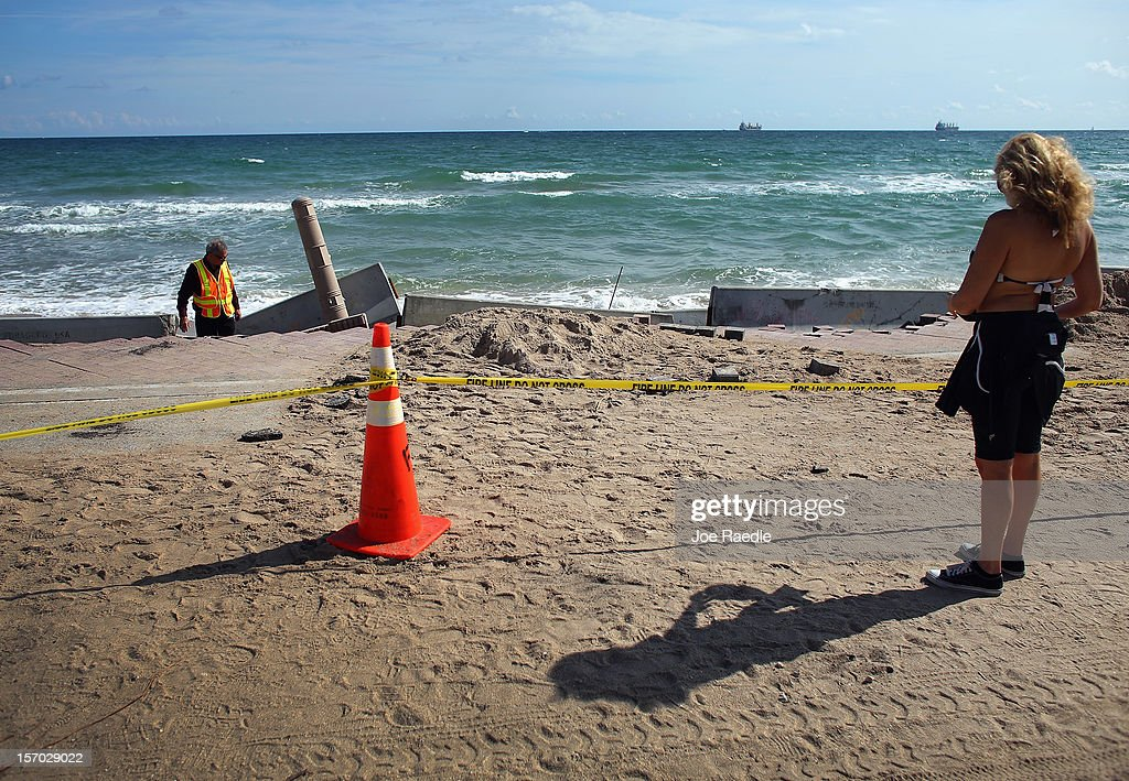 Florida Department of Transportation Operations Engineer, Cleo Marsh, (L) inspects the damage done to route A-1-A by the ocean, making parts of it impassable to vehicles on November 27, 2012 in Fort Lauderdale, Florida. The beach was eroded away last month when Hurricane Sandy passed by to the east and now City officials are saying that the damage may preview what rising sea levels can mean for coastal communities throughout South Florida. Climate scientists predict sea levels in South Florida will rise by 1 foot by 2070, 2 feet by 2115, and 3 feet by 2150.