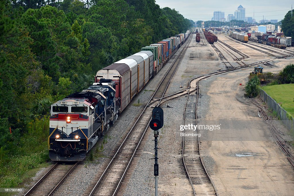 A Florida East Coast Railway (FEC) train departs the railway's Bowden Yard in Jacksonville, Florida, U.S., on Monday Sept. 23, 2013. The FEC is a 351-mile freight rail system along the east coast of Florida, connecting the ports of Miami, Fort Lauderdale and Palm Beach, which transports intermodal shipments, provides carload service and moves commodities, automobiles, bulk liquids, building materials, orange juice and electronics. Photographer: Mark Elias/Bloomberg via Getty Images