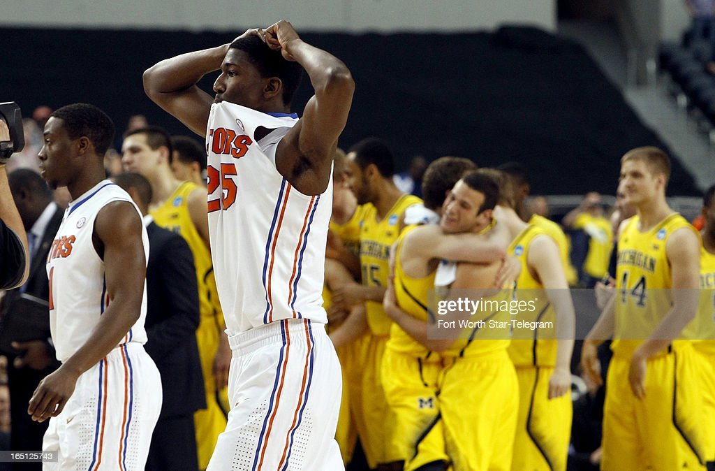 Florida Gators Kenny Boynton (1) and DeVon Walker (25) walk off the court after losing to the Michigan Wolverines, 79-59, during the NCAA Tournament at Cowboys Stadium in Arlington, Texas, Sunday, March 31, 2013.