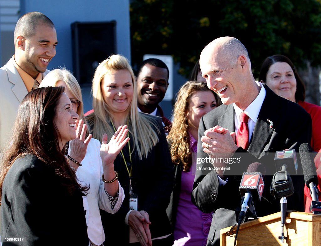 Florida Gov. Rick Scott chats with Ocoee Middle School principal Sharyn Gabriel, left, and other educators during the announcement of the governor's proposal to raise teacher pay statewide in the upcoming state budget, during a news conference at the school in Ocoee, Florida, on Wednesday, January 23, 2013.