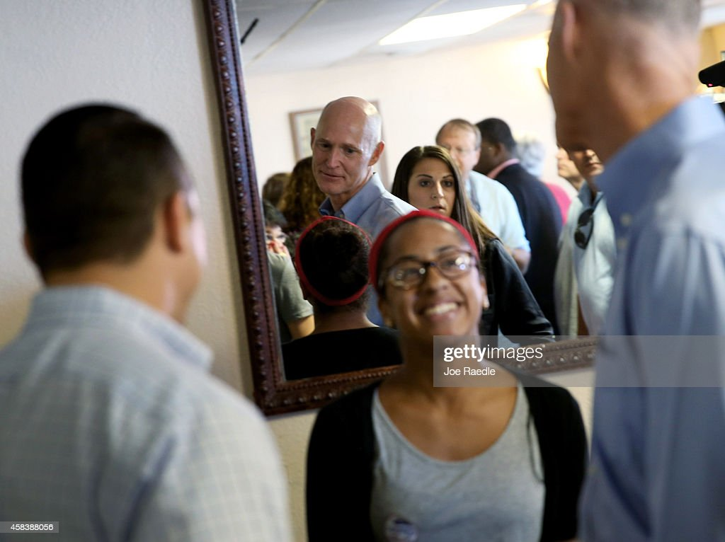 Florida Gov. Rick Scott is reflected in a mirror as he greets people while campaigning at the Arco-Iris Restaurant on November 4, 2014 in Tampa, Florida. Republican Governor Rick Scott is running against former Florida Governor Charlie Crist in the gubernatorial election.