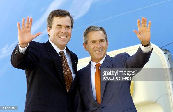 Florida Governor Jeb Bush and his brother US President George W Bush wave from atop the stairs to Air Force One shortly after a reading event for...