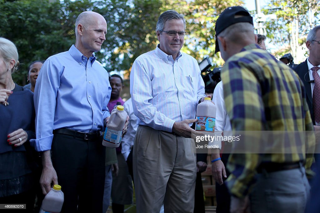 Florida Governor <a gi-track='captionPersonalityLinkClicked' href=/galleries/search?phrase=Rick+Scott+-+Politiek&family=editorial&specificpeople=2370892 ng-click='$event.stopPropagation()'>Rick Scott</a> (L) and Former Florida Governor <a gi-track='captionPersonalityLinkClicked' href=/galleries/search?phrase=Jeb+Bush&family=editorial&specificpeople=171487 ng-click='$event.stopPropagation()'>Jeb Bush</a> hand out items for Holiday Food Baskets to those in need outside the Little Havana offices of CAMACOL, the Latin American Chamber of Commerce on December 17, 2014 in Miami, Florida. Both governors reacted as they gave out food to the annoucement that the United States and Cuba worked out a deal for the release of USAID subcontractor Alan Gross.