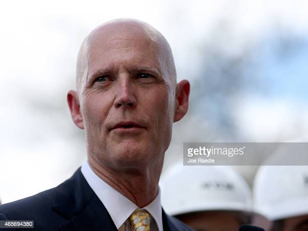 Florida Governor Rick Scott attends a road expansion event at the Casa Maiz restaurant as he fields questions from reporters about climate change on...