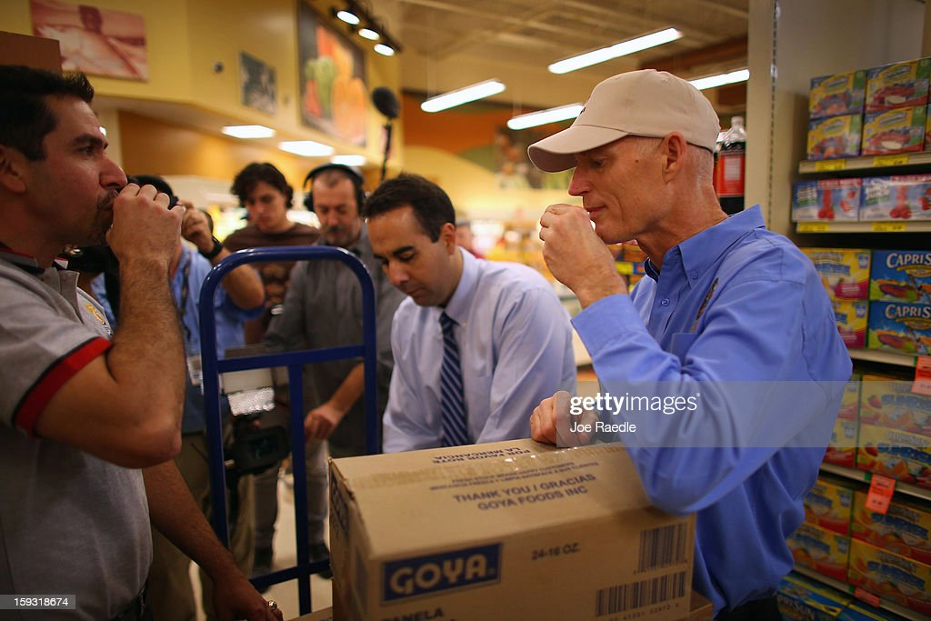 Florida Governor Rick Scott (R) drinks Cuban coffee with Jorge Rodriguez as they stock the shelves with Goya products at the Sedano's Supermarket on January 11, 2013 in Miami, Florida. Governor Scott spent his 15th 'Let's Get to Work Day' highlighting the importance of building up manufacturing jobs.