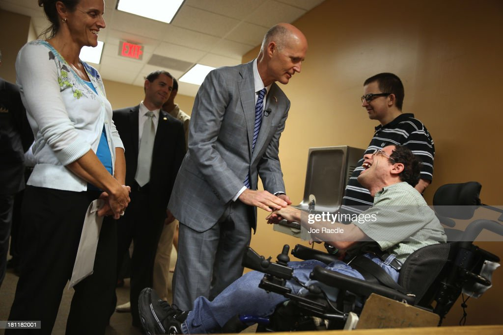 Florida Governor Rick Scott (C) greets Scott Dorfman as he arrives for a town hall meeting with the Agency for Persons with Disabilities (APD) at the Spelios Center, one of Sunrise Groups adult day training centers, to discuss issues impacting the greater disabilities community on September 19, 2013 in Miami, Florida. The Florida Governor leads the state that has refused to set up its own health care exchange in preparation for the Affordable Care Act, which is set to begin enrollment on October 1. Republican leaders in Florida have also highlighted concerns about the navigators, federally funded workers who will help enroll people in health plans.