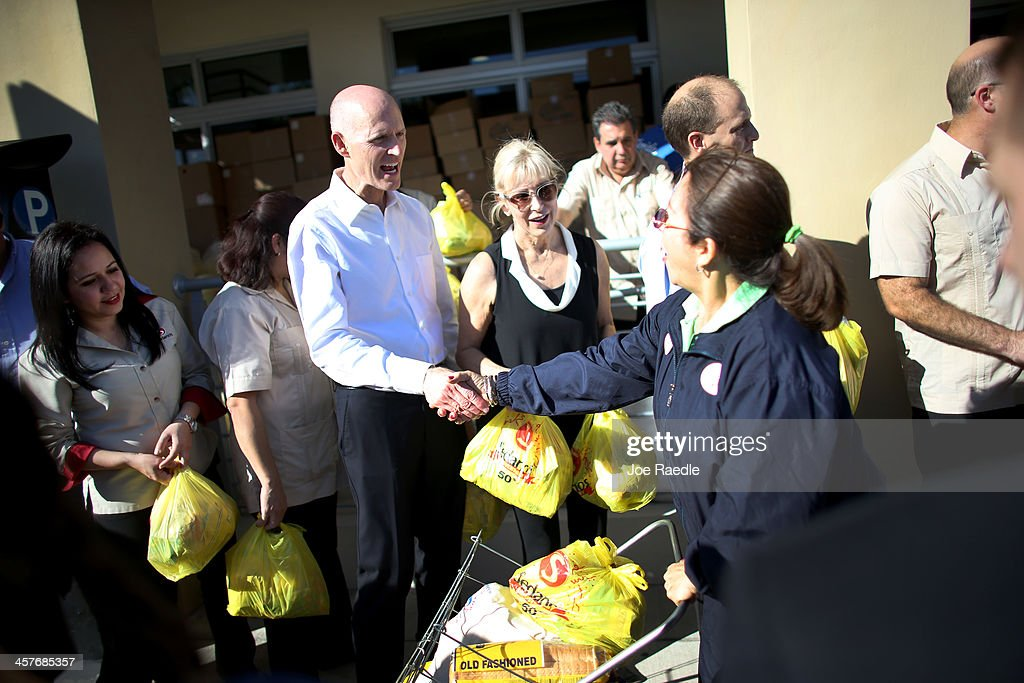 Florida Governor Rick Scott (3rd L) helps hand out holiday grocery supplies during a Latin American Chamber of Commerce sponsored event on December 18, 2013 in Miami, Florida. The chamber handed out 3,000 vouchers during the annual event several weeks ago and those with vouchers exchanged them today for bags of food worth up to $250. The meals include pork, yucca, milk, soda, and bread along with other items.