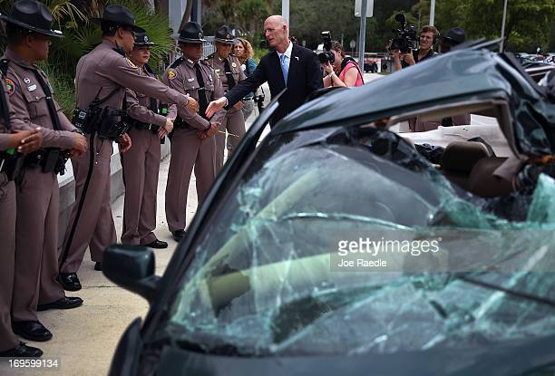 Florida Governor Rick Scott shakes hands with Florida Highway patrol officers near a wrecked car that is on display after he signed Florida Senate...