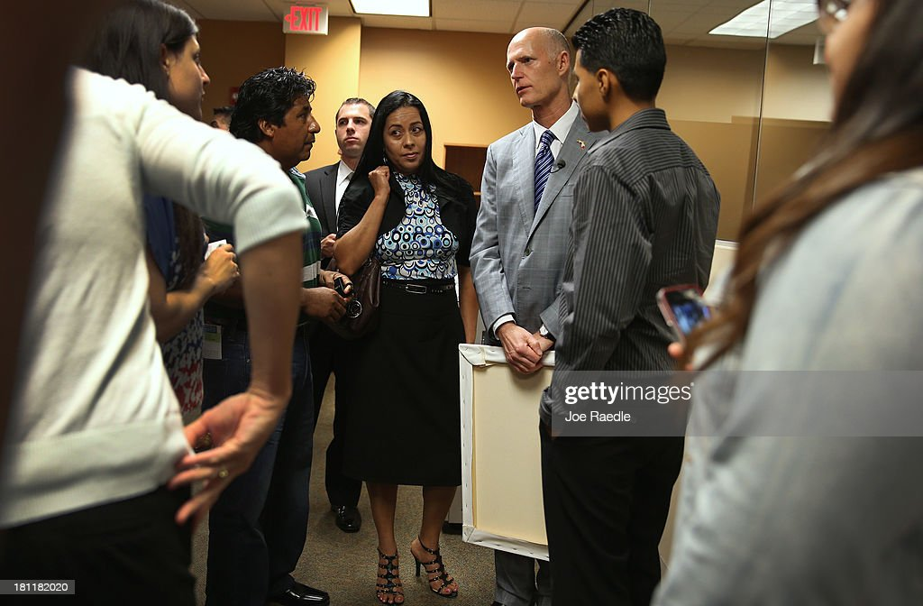 Florida Governor Rick Scott (2R) speaks with people as he arrives for a town hall meeting with the Agency for Persons with Disabilities (APD) at the Spelios Center, one of Sunrise Groups adult day training centers, to discuss issues impacting the greater disabilities community on September 19, 2013 in Miami, Florida. The Florida Governor leads the state that has refused to set up its own health care exchange in preparation for the Affordable Care Act, which is set to begin enrollment on October 1. Republican leaders in Florida have also highlighted concerns about the navigators, federally funded workers who will help enroll people in health plans.