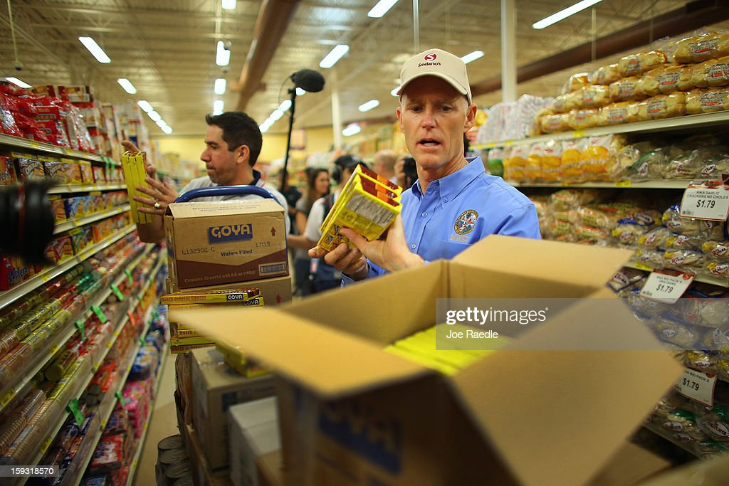 Florida Governor Rick Scott (R) unboxes Goya products at the Sedano's Supermarket as he helps restock the shelves on January 11, 2013 in Miami, Florida. Governor Scott spent his 15th 'Let's Get to Work Day' highlighting the importance of building up manufacturing jobs.