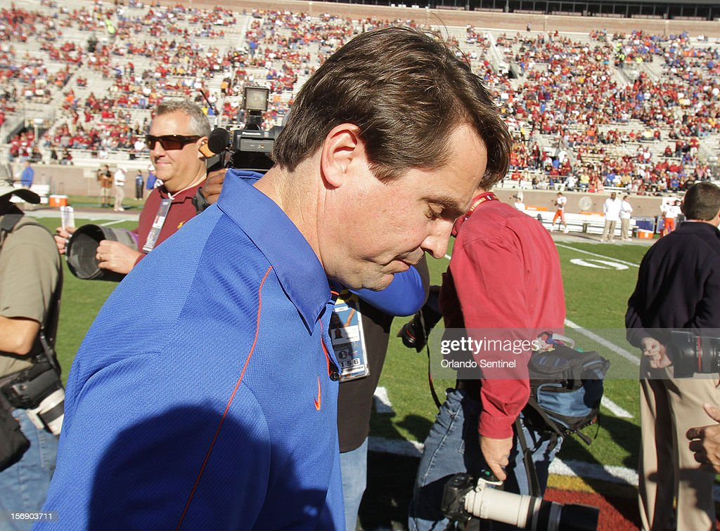 Florida head coach Will Muschamp ducks through photographers at midfield before the start of the Florida at Florida State football game at Doak Campbell Stadium in Tallahassee, Florida on Saturday, November 24, 2012.