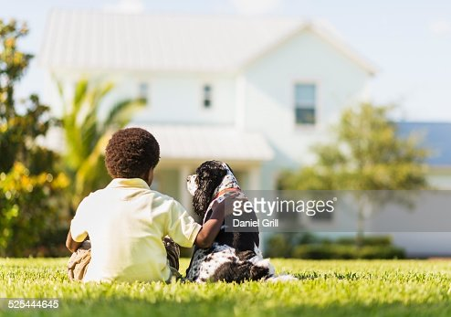 USA, Florida, Jupiter, Back view of boy (6-7 ) sitting with dog